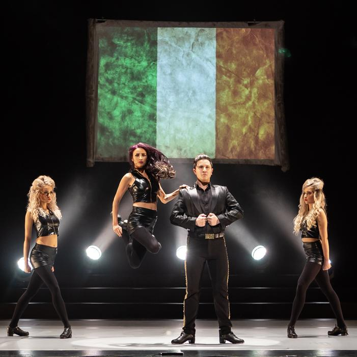 Image is of one male and three female dancers in dance pose on a stage with an Irish flag displayed behind them. White stage spotlights are shining up towards the flag.