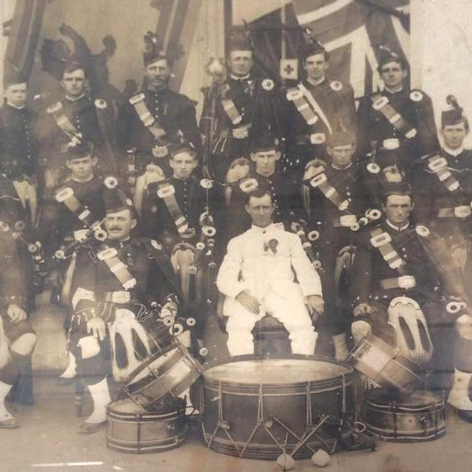 Image is in sepia tones with a group of male dark uniformed pipe band members sitting behind five carefully placed drums, man sitting centre in white uniform.