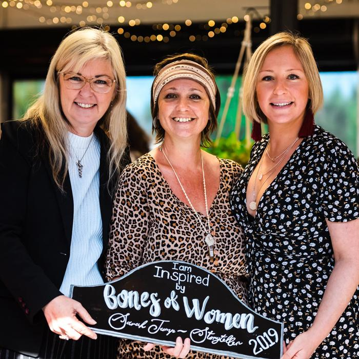 Image is of three smiling women holding a chalkboard with the words I am inspired by Bones of Women Sarah Trump Storyteller 2019