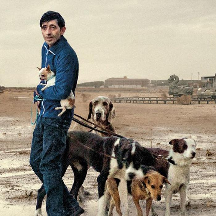 Image has a sepia coloured background of a sparse landscape with a dark haired man wearing blue denim jeans and jacket, holdina small dog under his arm and leading four other black, white and brown larger dogs.