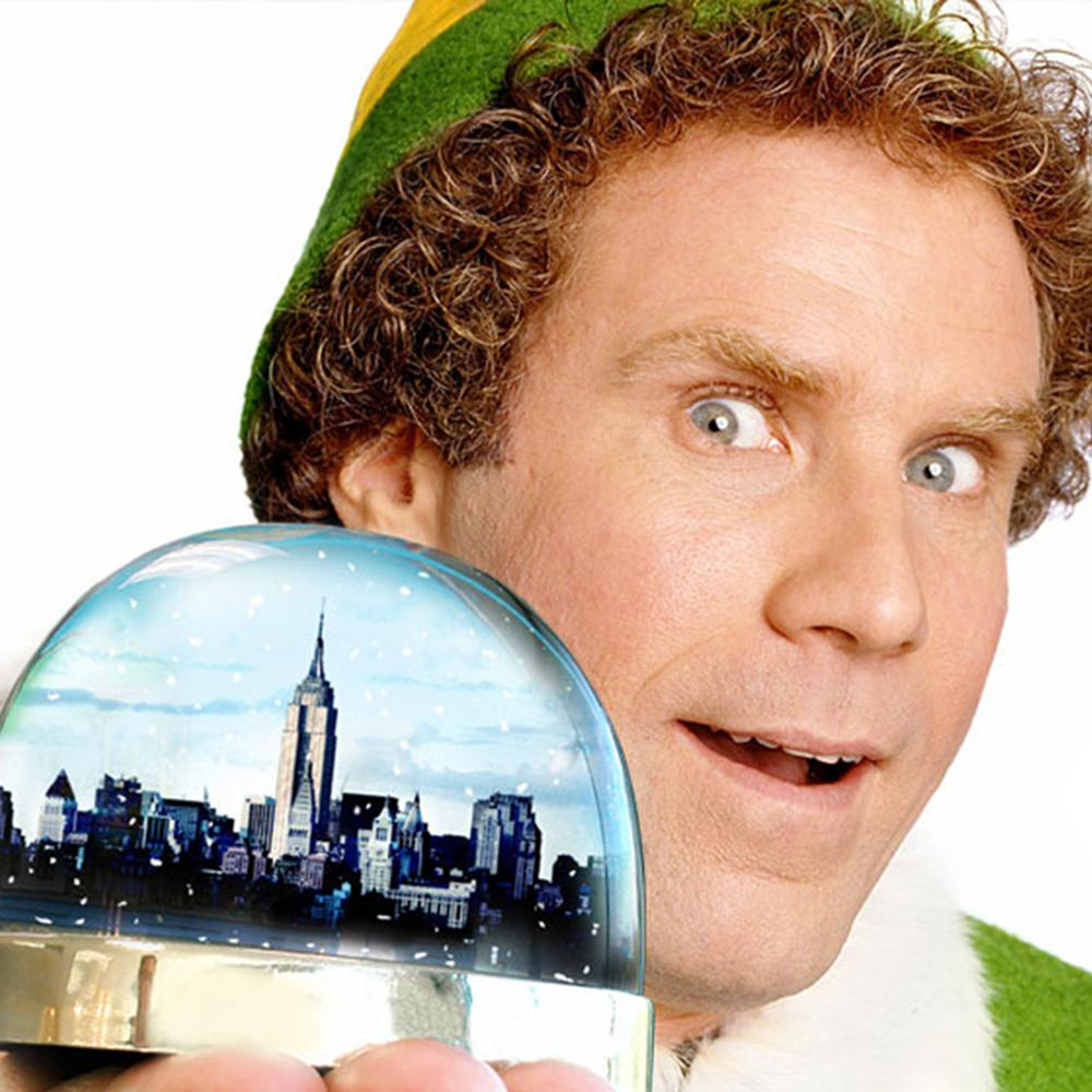 Image has a white background with the close up face of a man with blue eyes and light brown curly hair wearing a green and yellow elf hat holding a snow globe with an image of a city skyline inside.