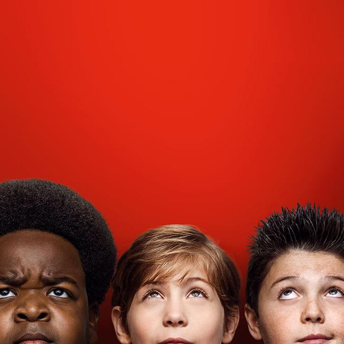 Image has a red background with the heads of three boys looking upwards.