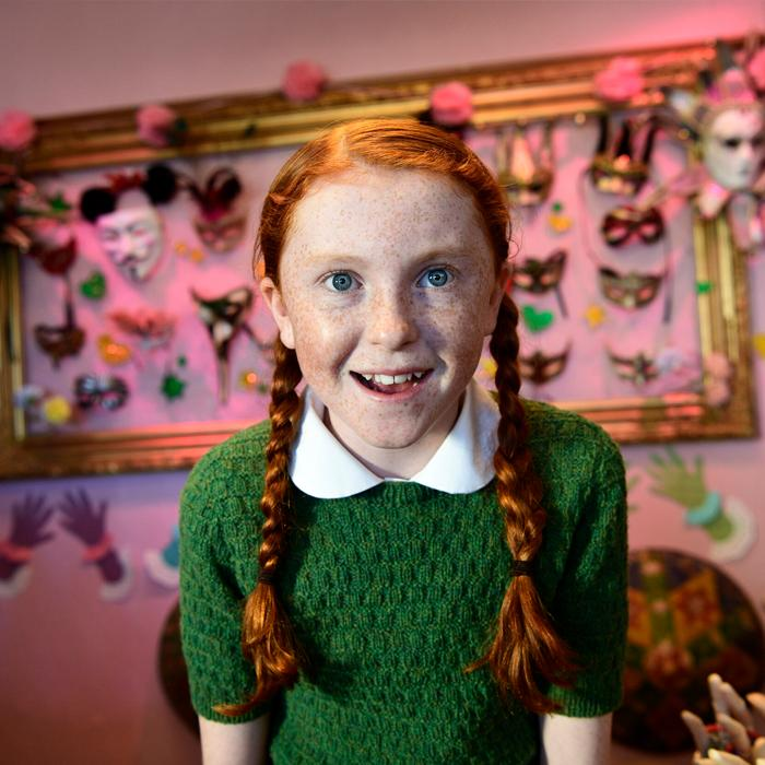Image is of an auburn, plaited, long haired girl wearing a green jumper and a white collared shirt. She has an open mouth smile. background is a blurred image of multi coloured theatre masks mounted on a picture frame.