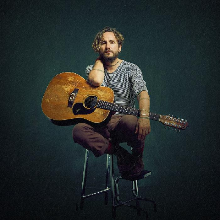Image has a dark background with a bearded man sitting on a high stool with his well-worn guitar resting on his lap. He is wearing a stripey shirt and brown long pants.