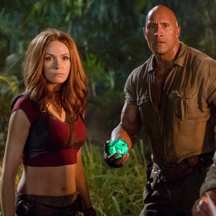 Image has a jungle backdrop with a bald man dressed in brown jungle wear holding a green glowing ball and a red haired female wearing red midi top and jungle pants. Both have serious expressions on their faces.