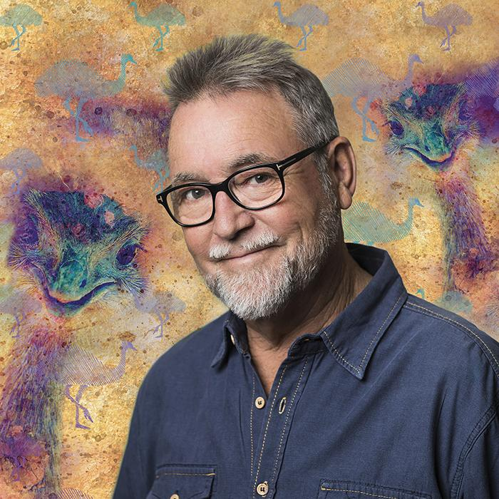 Image has an indigenous style painted background with two purple/green emu heads either side of a smiling, grey haired, bearded male wearing black glasses and blue denim shirt. Blue stripey images of whole emus are scattered over the rest of the image.