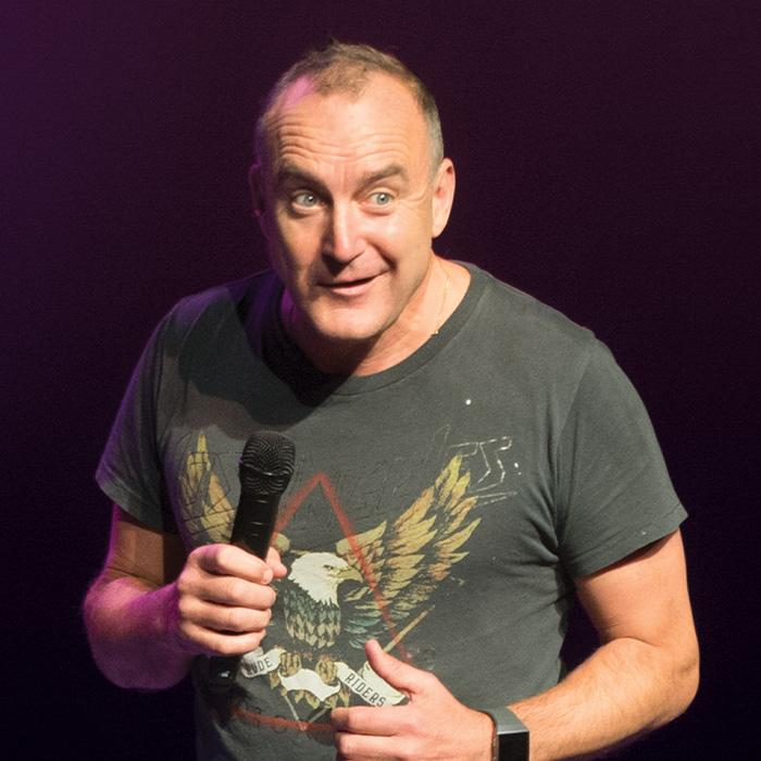 Image has a black background with a man wearing a grey shirt with an eagle in red triangle on the front holding a microphone and with a bemused expression on his face.