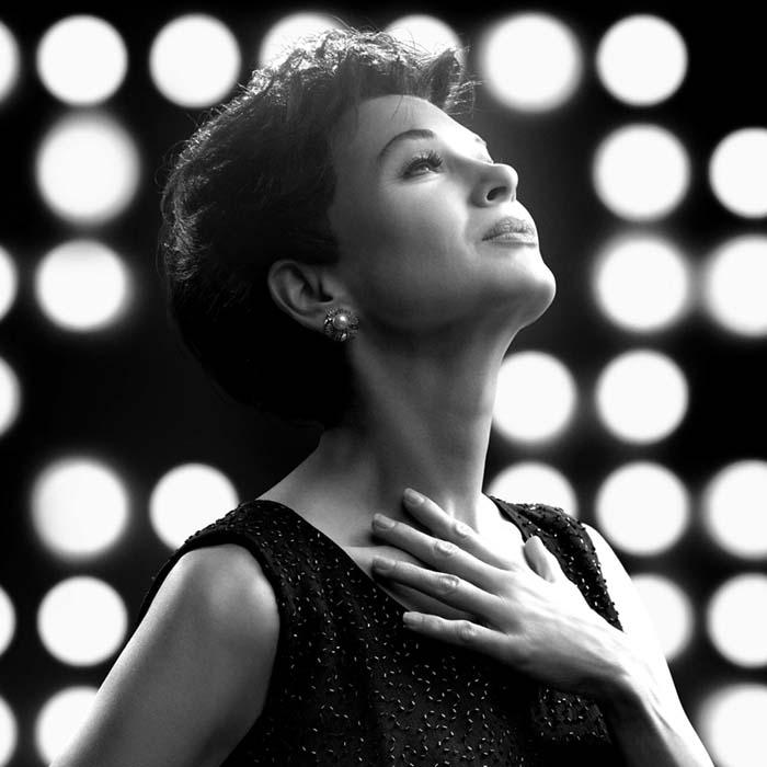 Image is black and white with unfocused white round stage lights as a background. In the foreground is a woman with short dark hair wearing a dark sleeveless dress with her hand on her chest looking upwards with her neck outstretched.