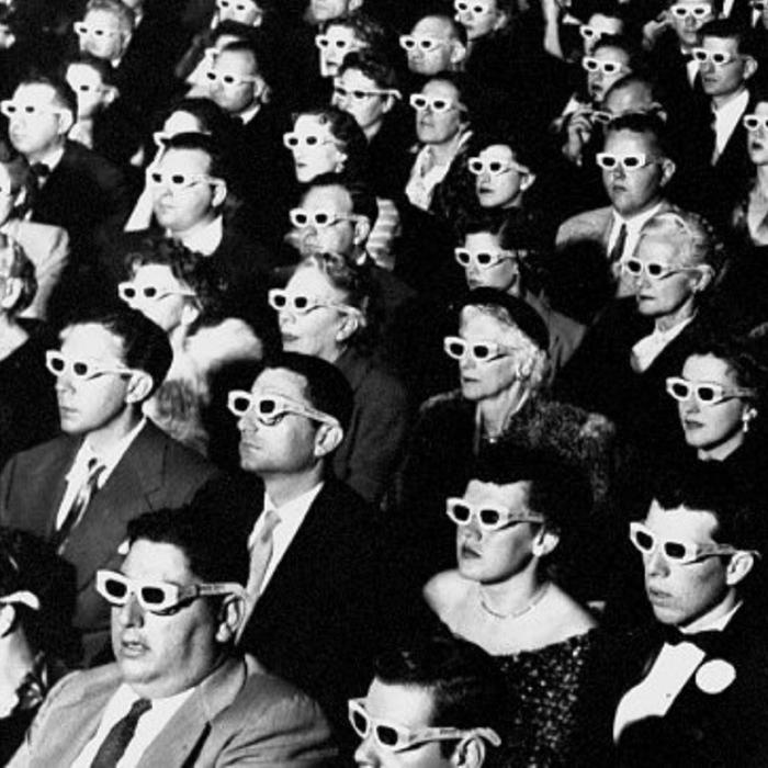 A black and white image of a seated audience of men and women dressed in formal theatre attire and wearing white 3D glasses.