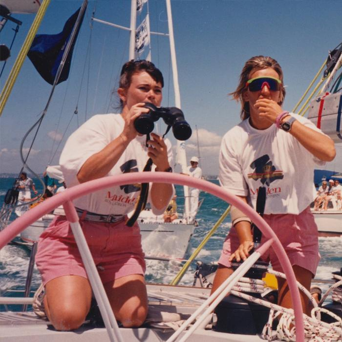 Image is of a partial sailboat with two women wearing white t-shirts and red shorts kneeling in front of a large steering wheel. One is holding binoculars.