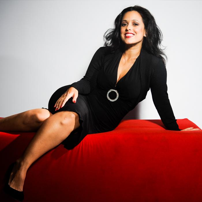 Image is of a smiling dark wavy haired lady in a black dress reclining on a red velvet cushiony box.