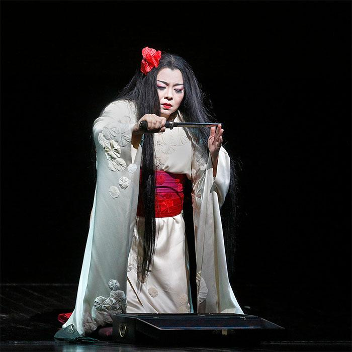 Image has a black background with a female dressed in a geisha themed white robe with blood red sash around her waist. She has long jet black hair with a red poppy like flower in her hair. Her arm is outstretched holding a knife.