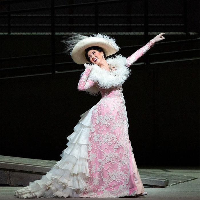 Image has a mostly black background with a smiling female wearing a powder pink lacy long sleeved gown with white ruffles at the back and white feathery neckline. She is holding a pose with arm outstretched looking back behind her.