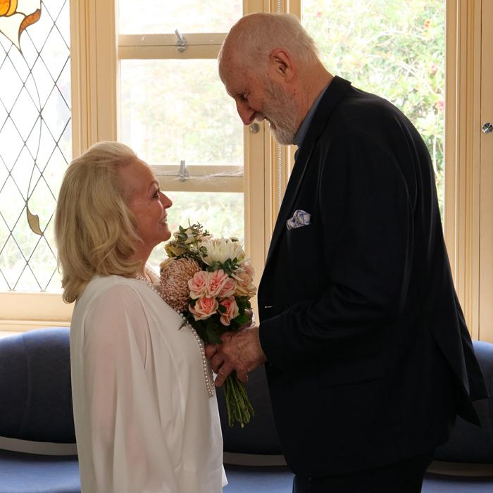 Image is of a tall elderly man and a shorter elderly lady standing facing eachother getting married. Both are smiling lovingly at eachother and the lady is holding a bouquet of white and pink flowers.
