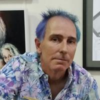 Image has a background of framed artwork with a man with two toned blue short spiky on top hair and a purple, green and blue flower and leaf patterned shirt.