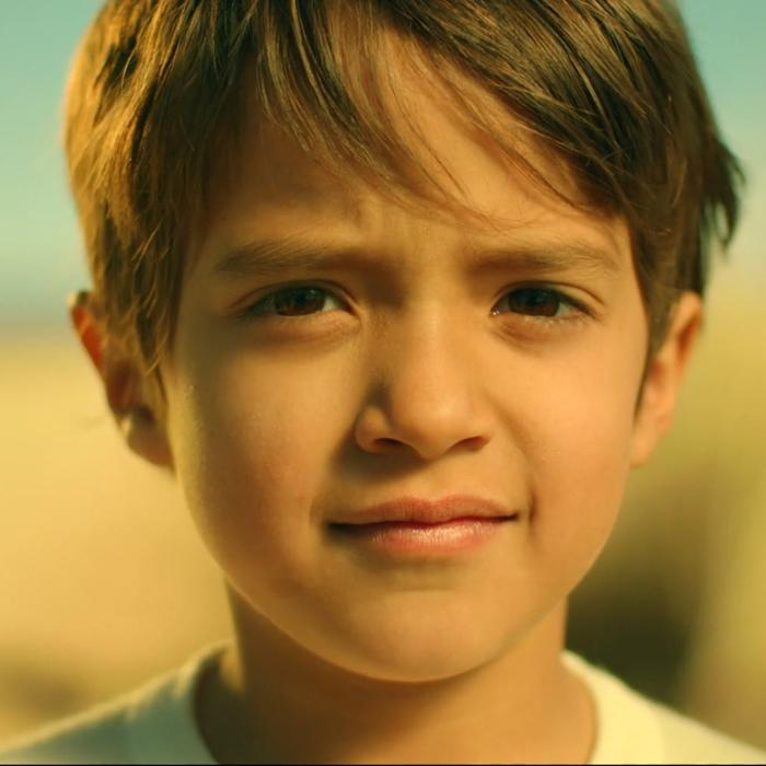 Image is of the head and shoulders of a light brown haired boy wearing a white t-shirt. He has a slight smile with a deep in thought expression.