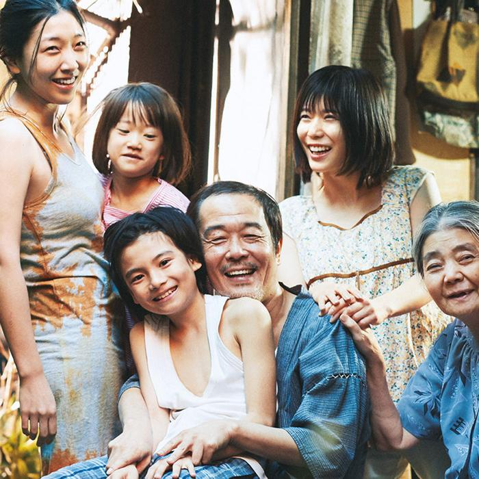 Image is of an Asian family consisting of three generations all smiling and laughing and standing/sitting close to eachother hugging and holding hands.