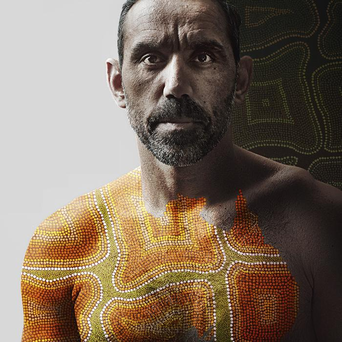 Image is of an Australian indigenous man with the map of Australia painted in Aboriginal design across his chest and right shoulder. The background is half white and half Aboriginal painting design.