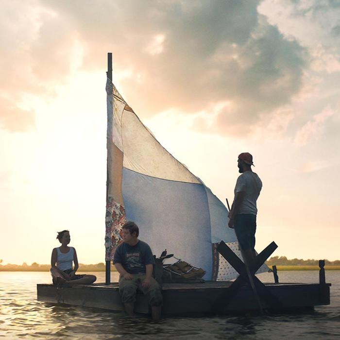Image has a background of a sunset/sunrise over land and  sea with two men and one women on a makeshift raft with a handmade sail.