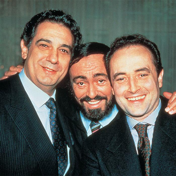 Image has a greeny grey backdrop with three dark haired, smiling men wearing dark suits, blue shirts and blue/grey ties. All heads are close together. The black bearded man in the middle has his arms around the two's shoulders.