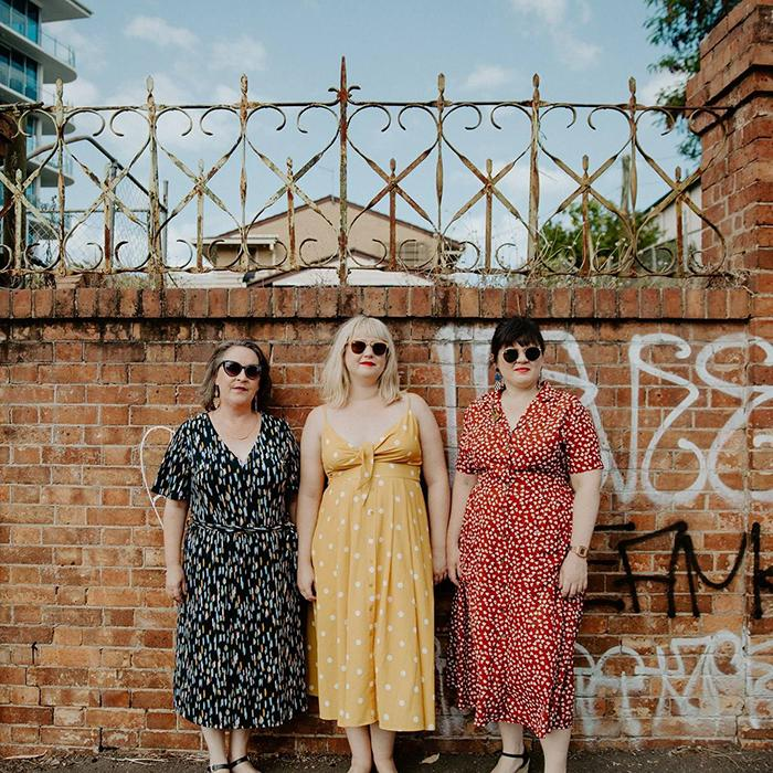 Image is of three ladies wearing sunglasses and summery dresses in front of a graffitied brick wall with cast iron fencing.