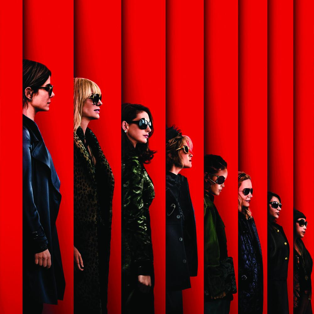 Image has a red paneled background with the side views of eight women dressed in classy dark clothes and wearing dark sunglasses.