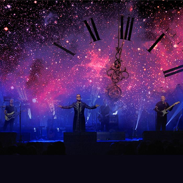 Image is of  a stage setting with four band members, three guitarists and one lead singer. The lighting is blue, purple and pink with white fairy lights scattered around. A partial clock with roman numerals is across the scene.